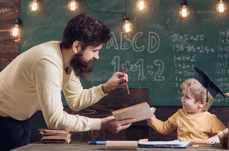 Teacher concept. Teacher read book to little school boy. Teacher man teach child in class. It is teachers who take us. Teacher concept. Teacher read book to royalty free stock photos