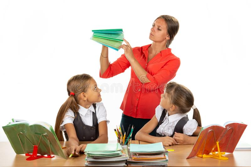 The teacher considers the notebooks of students, two schoolgirls look at her with interest royalty free stock photography