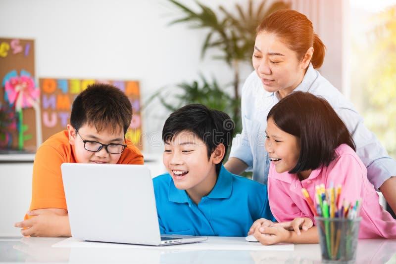 Teacher and Cute Asian children using laptop computer together. Asian women teacher and Cute Asian children are using laptop computer together stock image