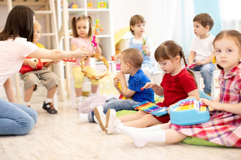 Teacher and cute kids during music lesson in preschool. Teacher and cute children during music lesson in preschool royalty free stock photography