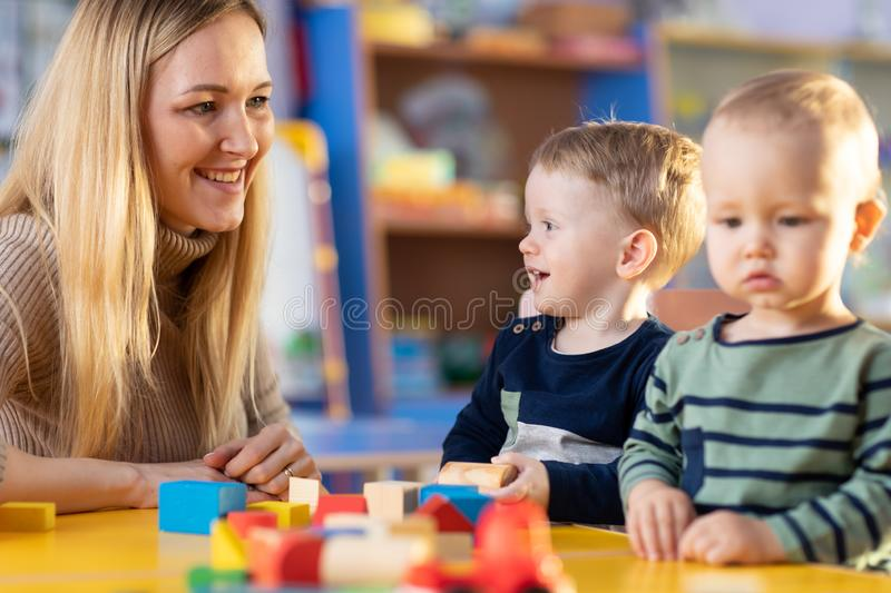 Teacher and cute little girl play with blocks toy in preschool royalty free stock photography