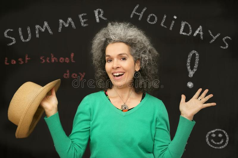 Teacher declaring beginning Summer Holidays. A happy mature female teacher with her hands up in front of a blackboard with text written on it. Last school day royalty free stock image