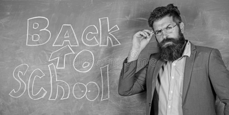 Teacher or educator welcomes students while stands near chalkboard with inscription back to school. Teacher begin first. Lesson after holidays. Invite to school royalty free stock photo