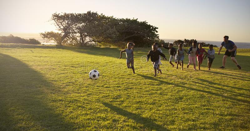 Teacher and elementary school kids play football in a field stock photos