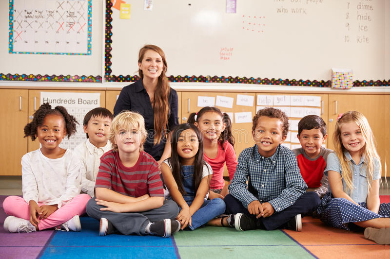 Teacher and elementary school kids sitting on classroom floor stock images
