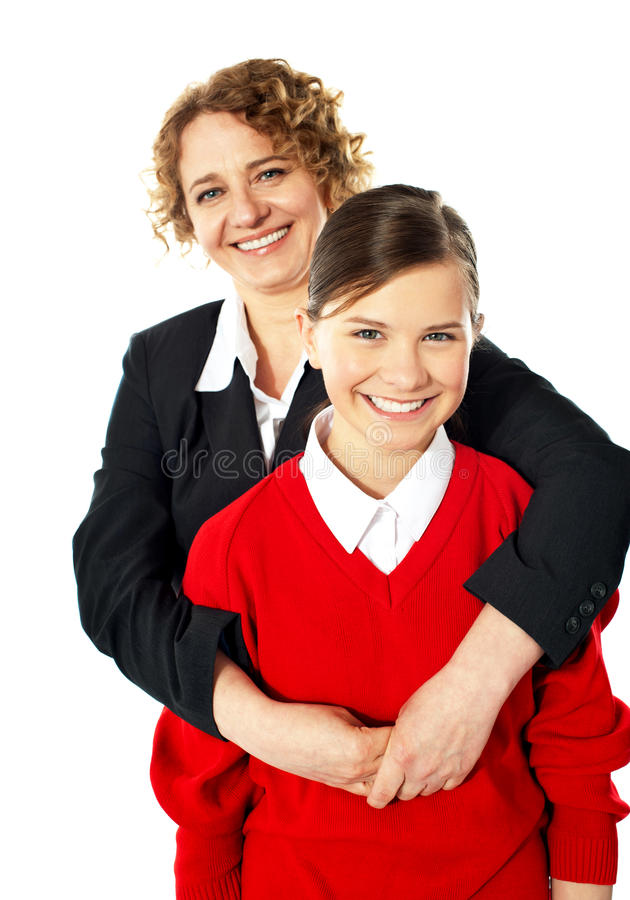 Teacher embracing her student from back. And posing in front of camera royalty free stock photos