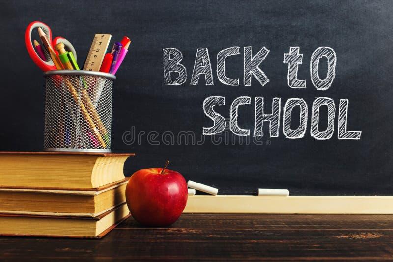 Teacher' escritorio de s con materiales de escritura, un libro y una manzana, un espacio en blanco para el texto o un fondo  imagenes de archivo