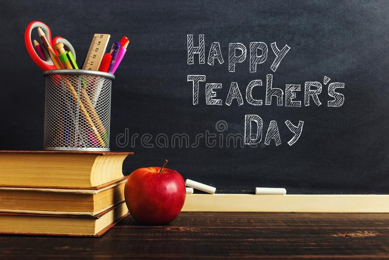 Teacher' escritorio de s con materiales de escritura, un libro y una manzana, un espacio en blanco para el texto o un fondo  imagen de archivo libre de regalías