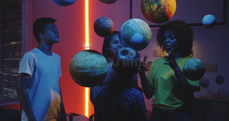 Teacher explaining astronomy to students. Medium shot of a young female teacher explaining astronomy to students with planet models stock photo