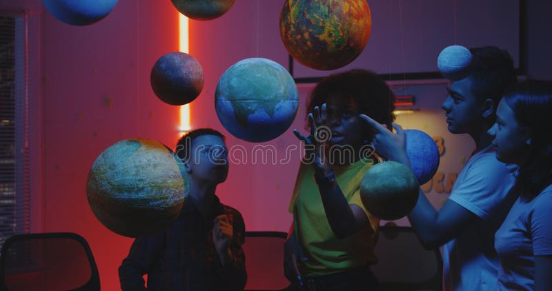 Teacher explaining astronomy to students. Medium shot of a young female teacher explaining astronomy to students with planet models stock image