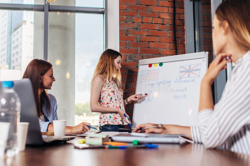 Teacher explaining differences between American and British spelling writing on whiteboard while adult students sitting royalty free stock photos