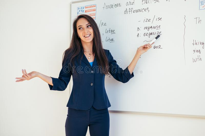 Teacher explaining differences between American and British spelling writing on whiteboard English language school.  royalty free stock images