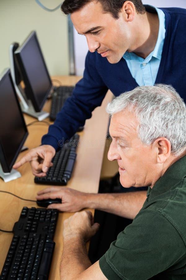 Teacher Explaining Senior Man In Computer Class royalty free stock images
