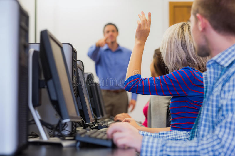 Teacher explaining to students in computer room. Teacher explaining to young college students in the computer room royalty free stock photos