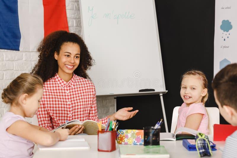 Teacher explaining vocabulary to the kids royalty free stock photos