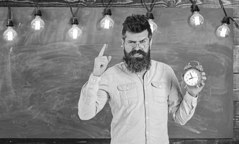 Teacher in eyeglasses holds alarm clock. Discipline concept. Bearded hipster holds clock, warning with index finger. Copy space. Man with beard and mustache on stock images