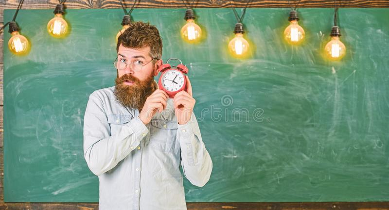 Teacher in eyeglasses holds alarm clock. Man with beard and mustache on concentrated face listening clock. Bearded royalty free stock images