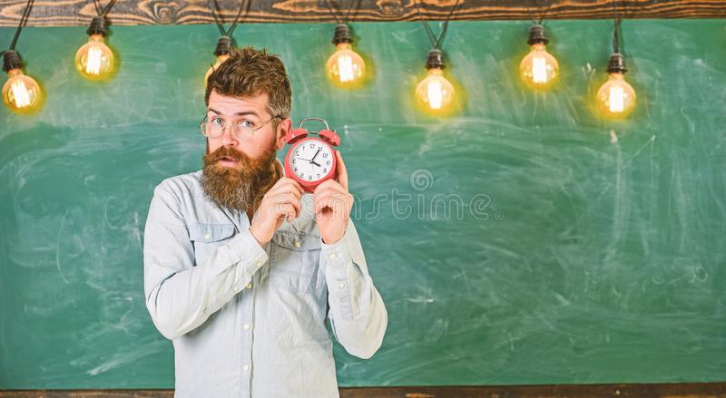 Teacher in eyeglasses holds alarm clock. Man with beard and mustache on concentrated face listening clock. School bell. Concept. Bearded hipster holds clock stock photos