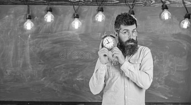 Teacher in eyeglasses holds alarm clock. Man with beard and mustache on concentrated face listening clock. School bell. Concept. Bearded hipster holds clock royalty free stock images
