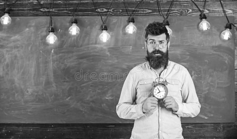 Teacher in eyeglasses holds alarm clock. Schedule and regime concept. Bearded hipster holds clock, chalkboard on royalty free stock photo