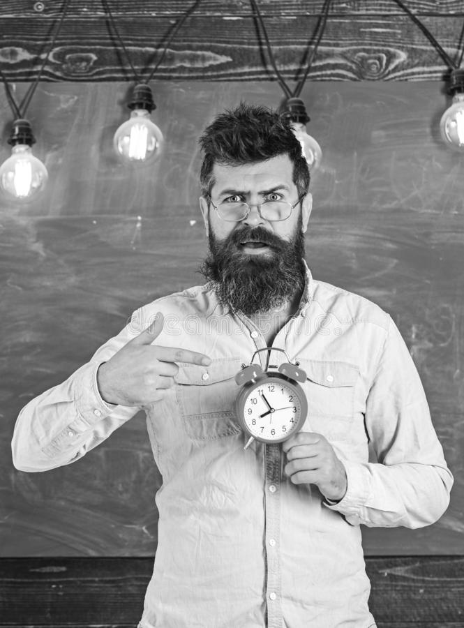 Teacher in eyeglasses holds alarm clock. Schedule and regime concept. Bearded hipster holds clock, chalkboard on royalty free stock images