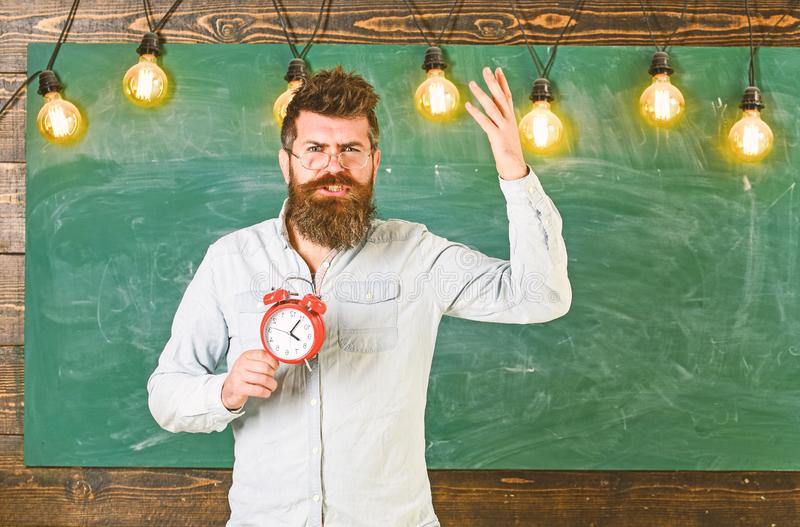 Teacher in eyeglasses holds alarm clock. Schedule and regime concept. Bearded hipster holds clock, chalkboard on stock images