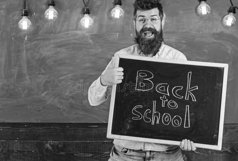 Teacher in eyeglasses holds blackboard with inscription back to school. Man with beard on happy face welcomes students. With thumb up gesture, chalkboard on royalty free stock photos