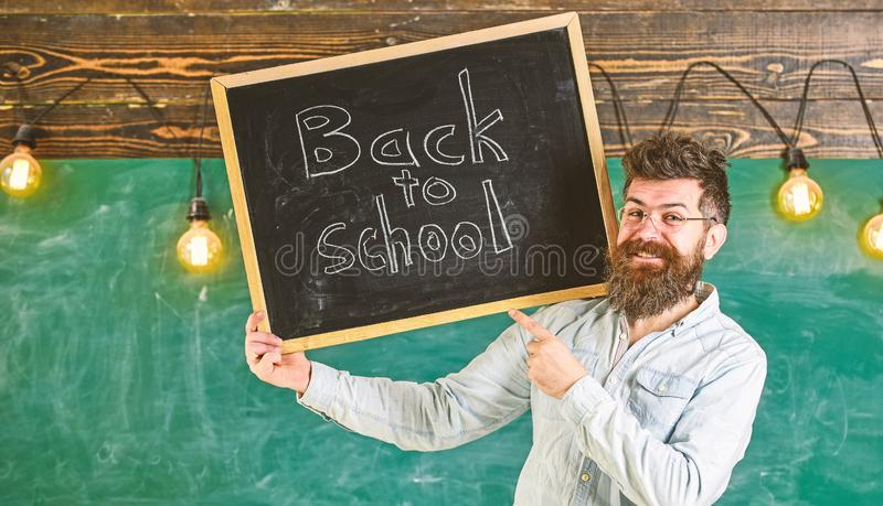 Teacher in eyeglasses holds blackboard with title back to school. Hiring teachers concept. Man with beard and mustache stock photos