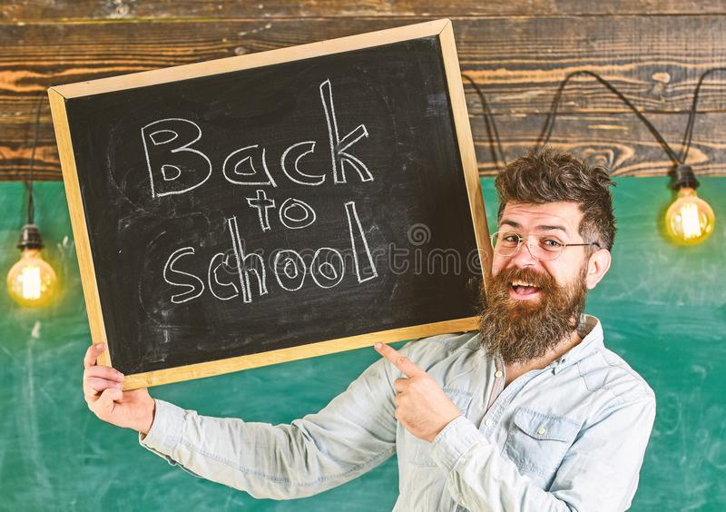 Teacher in eyeglasses holds blackboard with title back to school. Man with beard and mustache on happy face welcomes. Colleagues, chalkboard on background royalty free stock photo