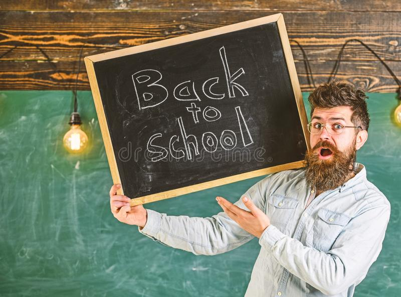 Teacher in eyeglasses holds blackboard with title back to school. Man with beard and mustache on surprised face welcomes. Students, chalkboard on background royalty free stock photos