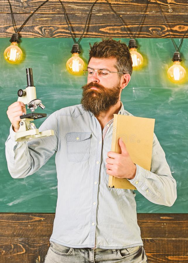 Teacher in eyeglasses holds book and microscope. Man with beard and mustache on strict face in classroom. Scientist. Holds book and microscope, chalkboard on royalty free stock photo