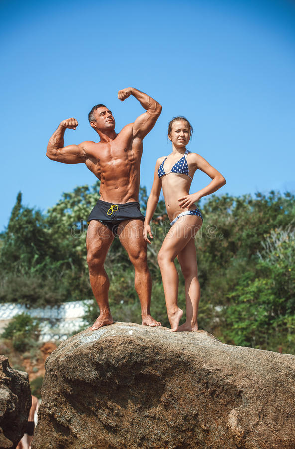 Teacher on fitness with the pupil on a beach stock image