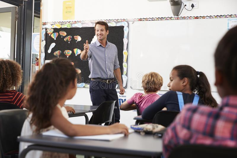 Teacher gesturing to class in an elementary school lesson royalty free stock photo