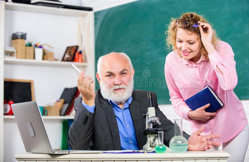 Teacher and girl with notepad near chalkboard. Biology science. Biologist or chemist with microscope teaching student royalty free stock photos