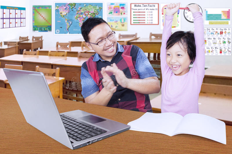 Teacher giving applause on his smart student. Portrait of young teacher giving applause on his female student while celebrating her winning in the classroom royalty free stock image
