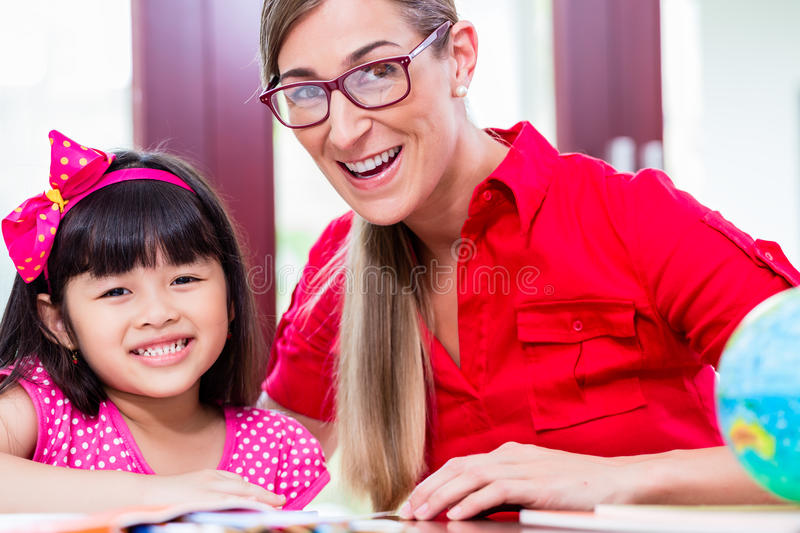 Teacher giving language lessons to Chinese child royalty free stock photos