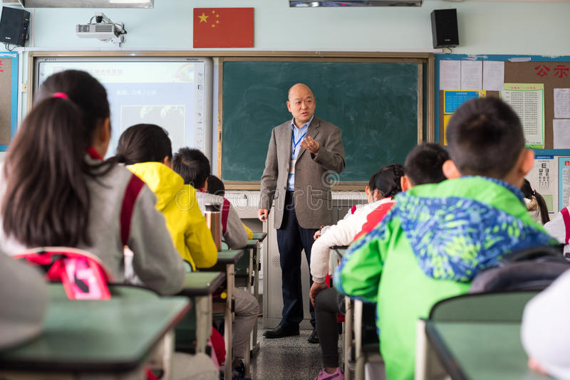 Teacher giving a lesson to children in a chinese classroom stock photos