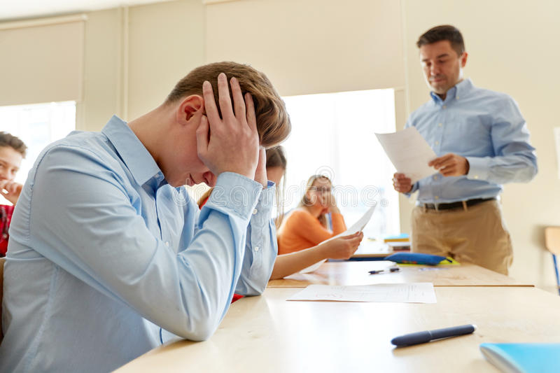 Teacher giving test results to group of students. Education, high school, learning and people concept - upset student boy and teacher with bad test results in royalty free stock photo