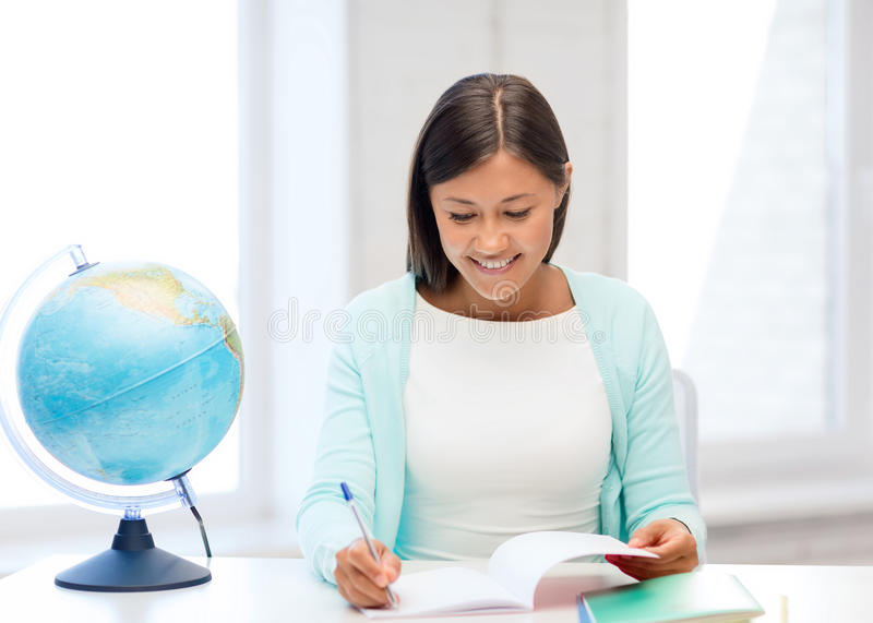Download Teacher With Globe And Notepad At School Stock Photo - Image: 34396904