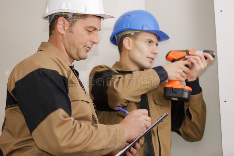Teacher grading apprentice drill. Teacher grading the apprentice drill stock images