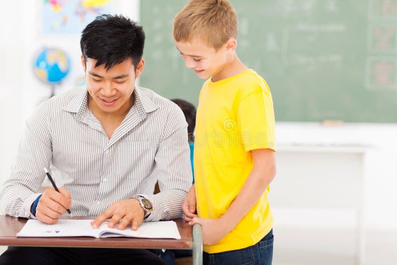 Teacher grading. Cheerful young male teacher grading school boy's work royalty free stock photos