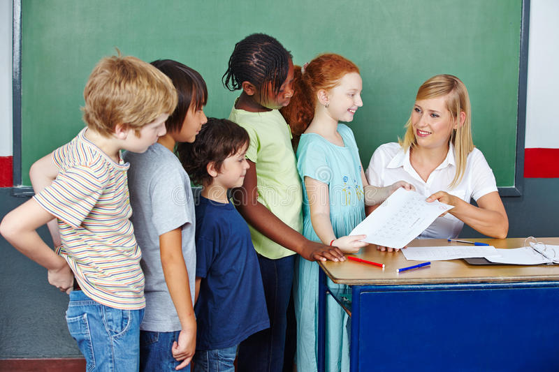Teacher grading tests for students. In elementary school at her desk royalty free stock photos