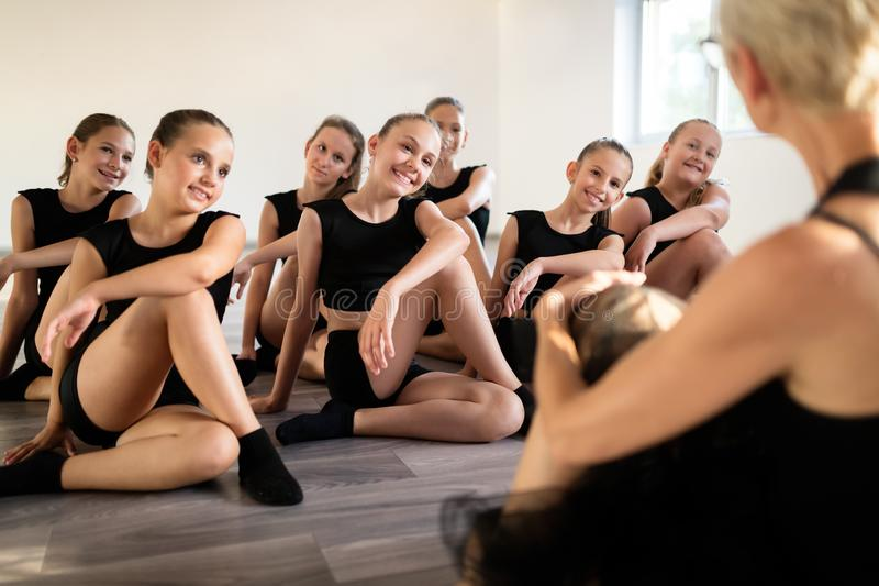 Teacher and group of children exercising dancing and ballet in dance school. Teacher and group of fit children exercising dancing and ballet in dance school stock images