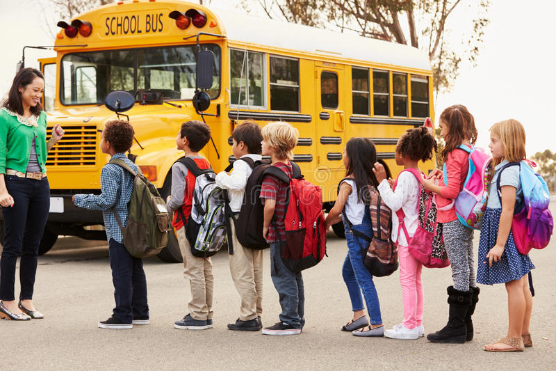 Teacher and a group of elementary school kids at a bus stop stock images