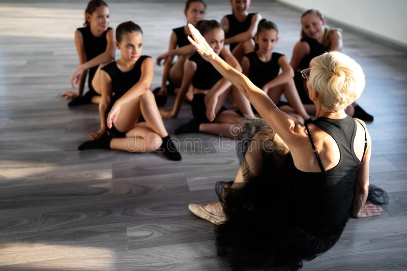 Teacher and group of children exercising dancing and ballet in dance school. Teacher and group of fit children exercising dancing and ballet in dance school stock photo
