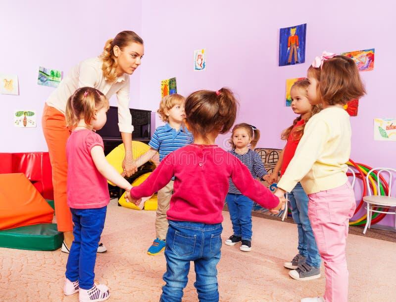 Teacher and group of kids in kindergarten stock images