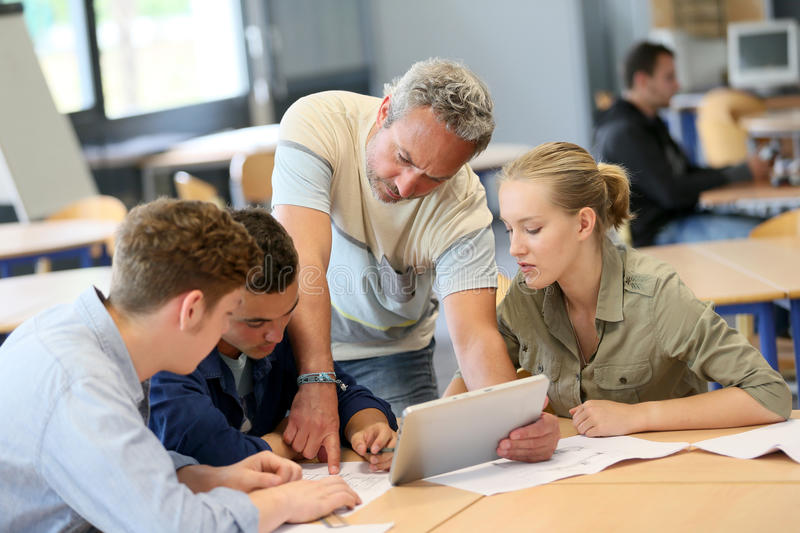 Teacher with group of students on tablet stock images