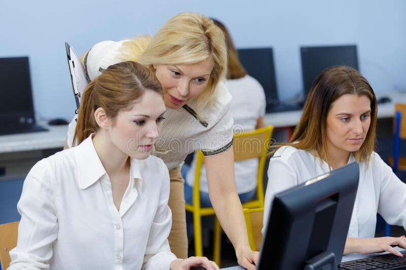 Teacher guiding teenage lady using computers stock photos