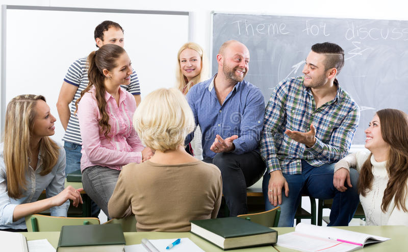 Teacher and happy adult students stock image