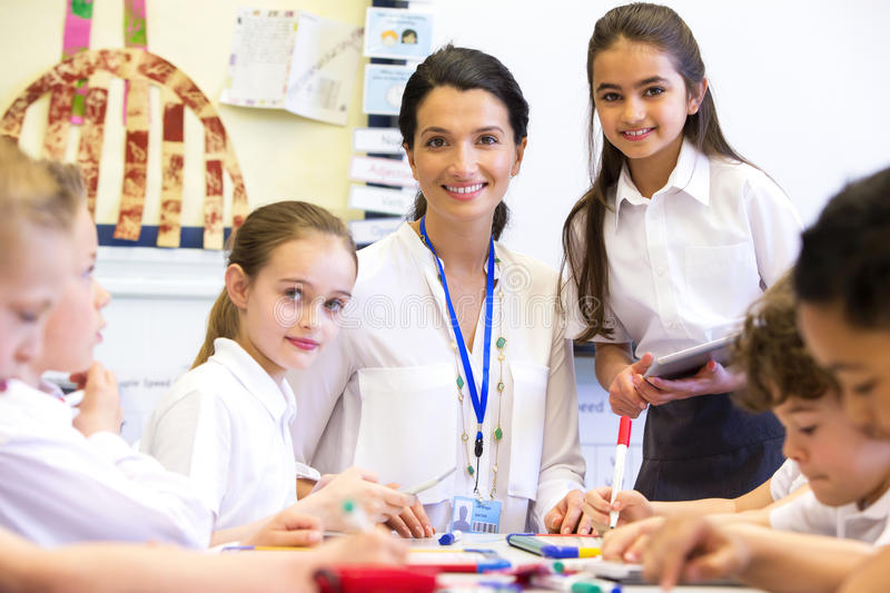 Teacher Happy at School. A female teacher and students are looking at the camera smiling. The image has been shot in a school classroom stock images